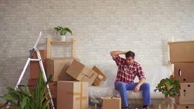 O homem com as grandes caixas em suas mãos cai no sofá