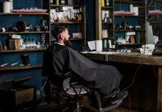 O homem com a barba coberta com o cabo preto senta-se na cadeira dos cabeleireiro na frente do espelho Homem com o cliente da bar foto de stock