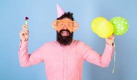 O homem com barba e bigode na cara feliz guarda balões de ar, luz - fundo azul Moderno em vidros gigantes Imagem de Stock