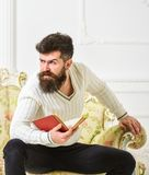 O homem com barba e bigode senta-se no sofá barroco do estilo, guarda o livro, fundo branco da parede Reflexões na literatura foto de stock
