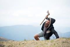 O homem com a barba na cara da gritaria conquista a parte superior da montanha com machado, fundo do céu Sobreviva no conceito se imagens de stock