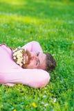 O homem com a barba na cara feliz aprecia a natureza Una com o conceito da natureza O homem farpado com as flores da margarida na foto de stock royalty free