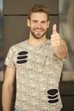 O homem com barba ou o indivíduo não barbeado na camisa à moda mostra o polegar acima Homem com a cerda na cara de sorriso na cam fotografia de stock