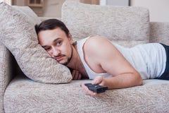 O homem com a barba realiza o fim de semana no sofá Fotos de Stock Royalty Free