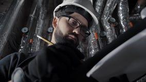 O homem com barba, suportes brancos vestindo do capacete em uma sala de caldeira, inspeciona filme