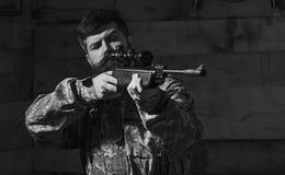 O homem com barba veste a roupa da camuflagem, fundo interior de madeira Macho na cara restrita na casa das guardas florestais imagens de stock royalty free