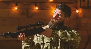 O homem com barba veste a roupa da camuflagem no fundo interior de madeira Macho na cara restrita na casa das guardas florestais imagens de stock