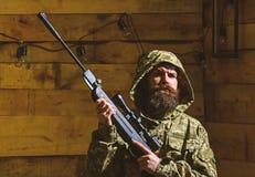 O homem com barba veste a roupa encapuçado da camuflagem, fundo interior de madeira Macho na cara restrita na casa das guardas fl imagens de stock