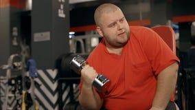 O homem com o barbell pesado nas mãos malha no gym vídeos de arquivo