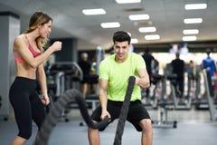 O homem com batalha ropes o exercício no gym da aptidão foto de stock royalty free