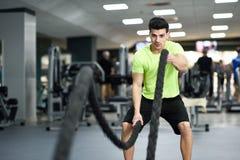 O homem com batalha ropes o exercício no gym da aptidão imagens de stock