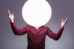 O homem com a bola grande da luz como a cabeça dá-lhe boas-vindas Foto de Stock Royalty Free