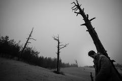 O homem com a cabeça pendurada inclinou os cotovelos em uma árvore inoperante imagem de stock
