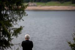 O homem com cabelo branco que olha fixamente no lago molha fotos de stock royalty free