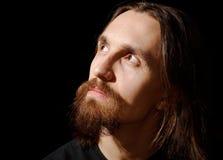 O homem com cabelo longo e a barba que olha acima e sairam Imagem de Stock Royalty Free