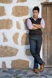 O homem com calças de brim aproxima uma porta rural Imagem de Stock