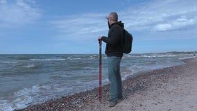 O homem com caminhada cola na praia perto do mar vídeos de arquivo