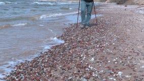 O homem com caminhada cola o passeio ao longo da borda do mar video estoque