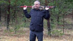 O homem com caminhada de varas aquece-se na floresta vídeos de arquivo