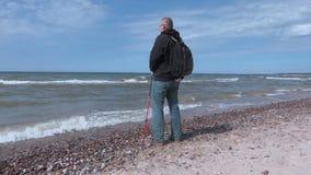 O homem com caminhada de varas mantém as mãos acima na praia perto do mar video estoque