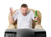 O homem com cerveja em uma poltrona presta atenção à tevê Imagens de Stock