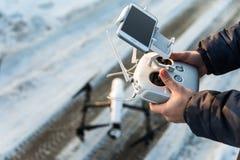 O homem com controlo a distância prepara a câmara digital branca do zangão para o voo do começo Fotografia de Stock