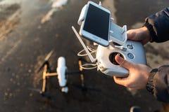 O homem com controlo a distância prepara a câmara digital branca do zangão para o voo do começo no inverno Foto de Stock