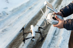 O homem com controlo a distância prepara a câmara digital branca do zangão para o voo do começo no inverno Foto de Stock Royalty Free