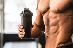 O homem com corpo perfeito guarda o abanador da proteína no gym após o exercício fotografia de stock