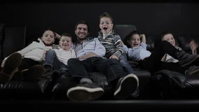 O homem com crianças está colocando no sofá no cinema filme