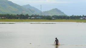 O homem com cubeta anda na água do rio contra nuvens do céu dos montes video estoque