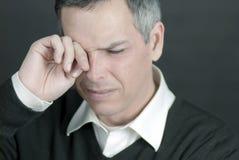 O homem com enxaqueca fricciona os olhos Fotos de Stock Royalty Free