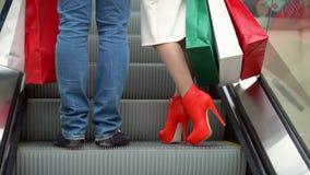 O homem com a escalada que da mulher a escada rolante com cor grande empacota Compras para o Natal Pés de pares novos no filme