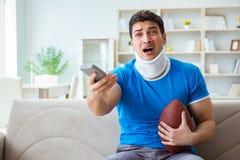 O homem com ferimento do pescoço que olha o futebol americano em casa fotografia de stock