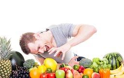 O homem com fome agarra frutas e legumes Imagem de Stock