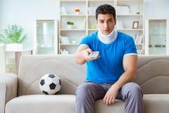 O homem com futebol de observação do futebol de ferimento do pescoço em casa fotos de stock royalty free