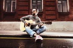 O homem com guitarra senta-se na beira da estrada Fotografia de Stock Royalty Free