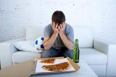 O homem com jogo de futebol de observação da garrafa da pizza e de cerveja da bola na coberta da tevê eyes triste e desapontado p Fotos de Stock