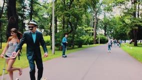 O homem com o bigode em óculos de sol do revestimento de jantar monta no skate na estrada no parque filme