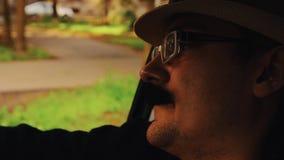 O homem com o bigode no chapéu, vidros que sentam-se no carro e canta parody hipster video estoque