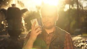 O homem com o telefone perto da fonte no por do sol filme