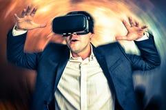 O homem com os óculos de proteção da realidade virtual está jogando os jogos 3D Imagem de Stock Royalty Free