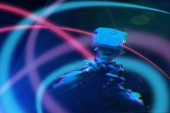 O homem com os auriculares da realidade virtual est? jogando o jogo Imagem com efeito do pulso aleat?rio imagem de stock