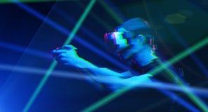 O homem com os auriculares da realidade virtual est? jogando o jogo Imagem com efeito do pulso aleat?rio fotografia de stock