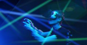 O homem com os auriculares da realidade virtual est? jogando o jogo Imagem com efeito do pulso aleat?rio fotos de stock royalty free