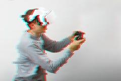O homem com os auriculares da realidade virtual est? jogando o jogo Imagem com efeito do pulso aleat?rio foto de stock royalty free