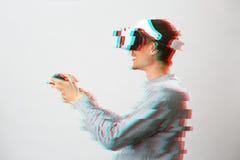 O homem com os auriculares da realidade virtual est? jogando o jogo Imagem com efeito do pulso aleat?rio foto de stock