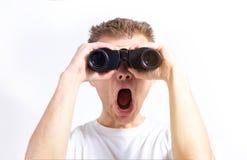 O homem com os binóculos nas mãos em um fundo branco isolou a vista da câmera foto de stock royalty free