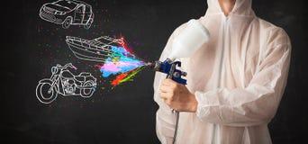 O homem com pintura à pistola do aerógrafo com carro, o barco e a motocicleta tiram Foto de Stock Royalty Free