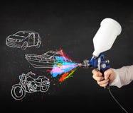 O homem com pintura à pistola do aerógrafo com carro, o barco e a motocicleta tiram Fotografia de Stock